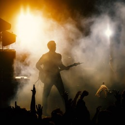 Silhouette of guitar player, guitarist perform on concert stage. Dark background, smoke, concert spotlights.